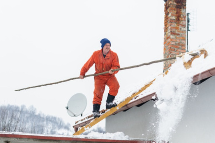 man raking snow from roof - no fall arrest equipment